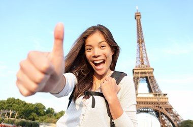 Happy tourist at the Eiffel tower, Paris. Europe Travel Insurance.