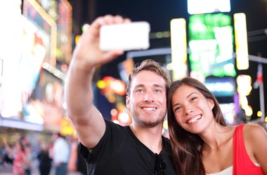 Couple taking selfie at Times Square, New York. Travel Insurance for America.