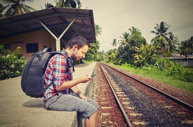 Young traveller waiting for a train. Cheap travel insurance with all the benefits you need.